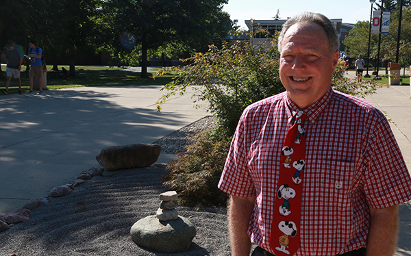 Dr. Mark Kleffner stands near the campus zen garden made of rocks he helped students collect.